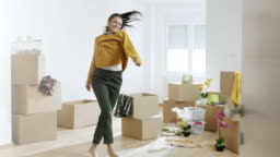 Woman unpacking things from boxes and dancing in her new home