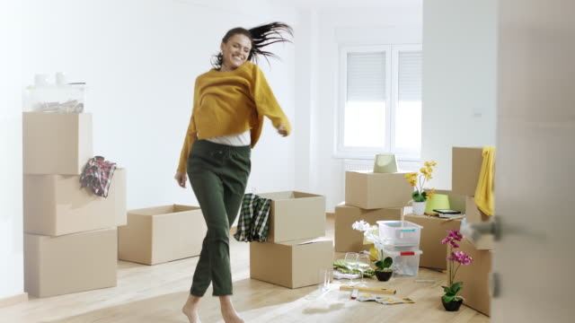 woman unpacking things from boxes and dancing in her new home - piacere video stock e b–roll