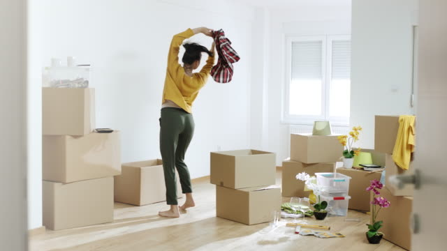 woman unpacking things from boxes and dancing in her new home - wooden floor stock videos & royalty-free footage