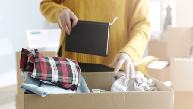 woman unpacking things from cardboard box - physical activity stock videos & royalty-free footage