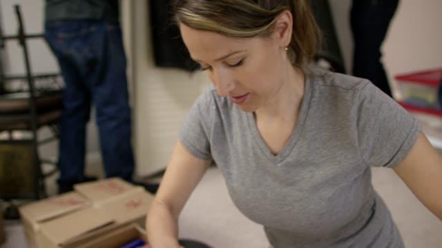 woman unpacks a moving box - tearing stock videos & royalty-free footage