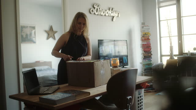 woman unpacks home delivery in loft apartment. - carrying stock videos & royalty-free footage