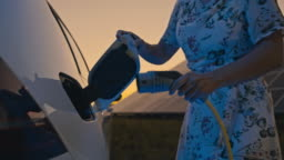 SLO MO Woman unplugging an EV plug after charging of her car had completed