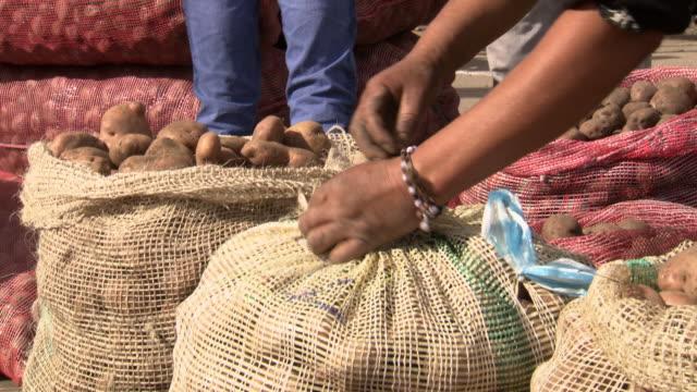 CU of woman untying and opening sack of potatoes, Villa De Leyva market, Villa De Leyva, Boyacá department, Colombia