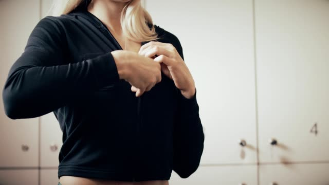 woman unzipping hooded top in locker room - absence stock videos & royalty-free footage