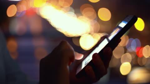 kvinnan använder en telefon i en stad - upptagen bildbanksvideor och videomaterial från bakom kulisserna