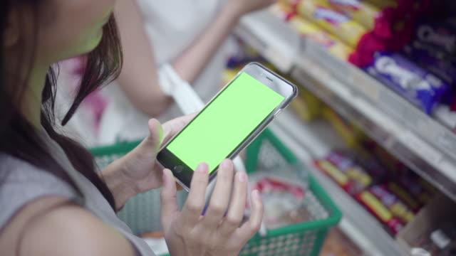 vídeos de stock, filmes e b-roll de mulher usar um telefone inteligente com tela verde na loja de departamentos. - send