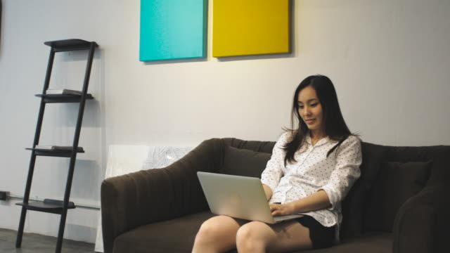 woman use computer on sofa - 30 34 years video stock e b–roll