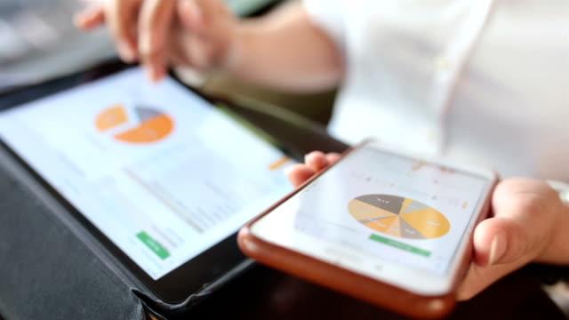 vídeos y material grabado en eventos de stock de mujer use teléfono inteligente y tableta digital en café - hoja de cálculo