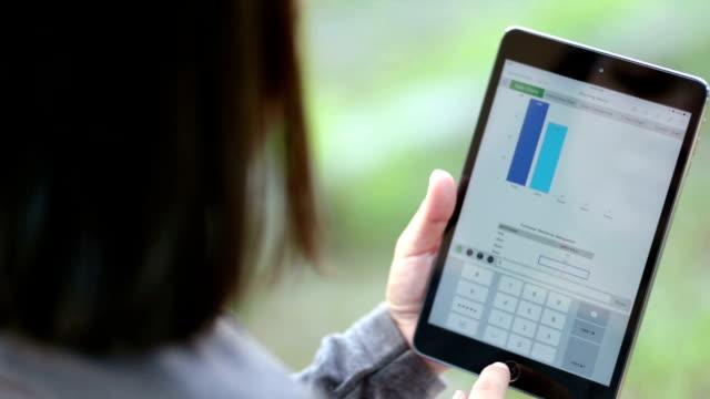 vídeos y material grabado en eventos de stock de mujer uso tableta digital en el jardín - hoja de cálculo