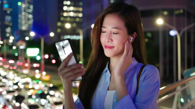 frau verwenden ohrknospen im freien - schnurloses telefon stock-videos und b-roll-filmmaterial