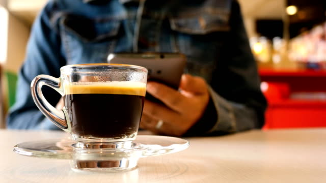 woman use smart on coffee shop and drink black coffee - coffee drink stock videos & royalty-free footage