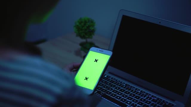 Frau zu verwenden, Smartphone und grünen Laptopbildschirm