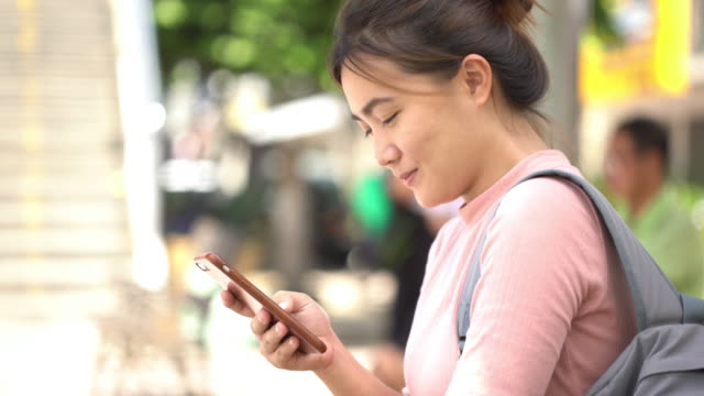 woman use smart phone at bus stop - bus stop stock videos & royalty-free footage