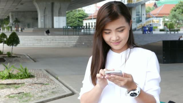 vídeos y material grabado en eventos de stock de mujer use teléfono inteligente en el parque - asociación norteamericana de telecomunicaciones e internet