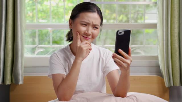 stockvideo's en b-roll-footage met de vrouw gebruik slimme telefoon in slaapkamer - alleen één tienermeisje