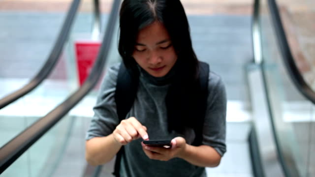 Woman use smart phone in city escalator