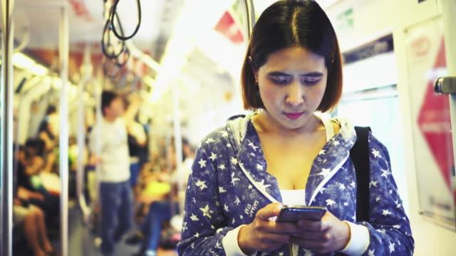 vídeos de stock, filmes e b-roll de telefone inteligente uso de mulher no trem. - smart