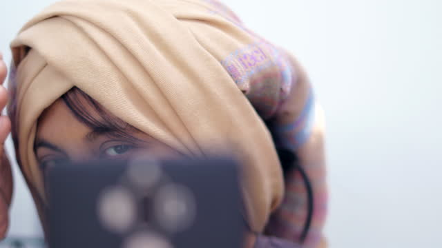 woman use smart phone to see her scarf on hair and selfie - covering stock videos & royalty-free footage