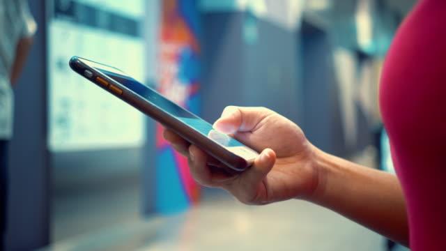 vídeos y material grabado en eventos de stock de mujer uso smartphones en almacén - gran almacén