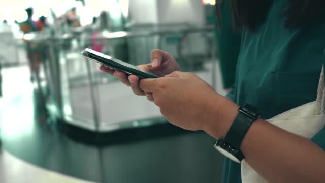 vídeos de stock, filmes e b-roll de mulher usa smartphone em loja de departamentos - shopping center