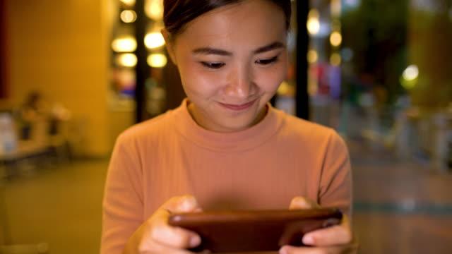 女性がレストランでスマート フォンを使用してください。 - 通信点の映像素材/bロール