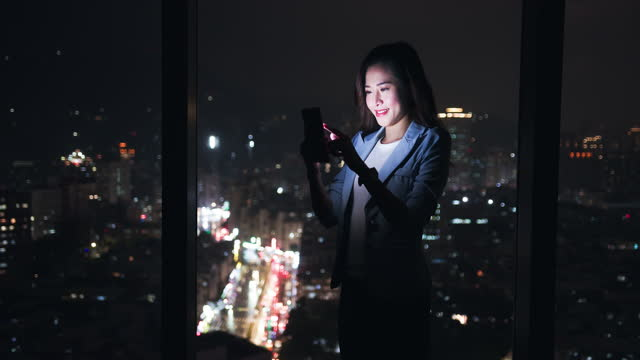 woman use smartphone near window - video stock videos & royalty-free footage