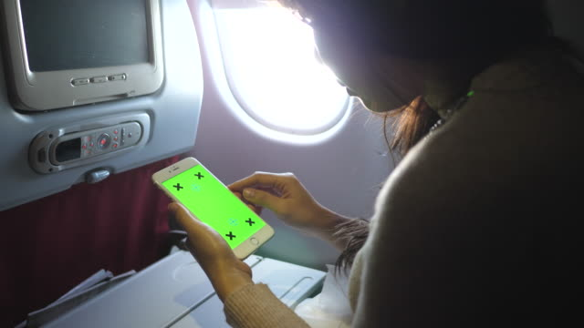 woman use smartphone on plane - messaggio video stock e b–roll