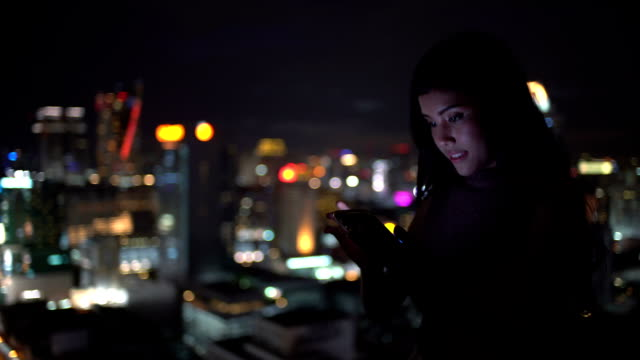 Woman use smartphone very happy for communicate including connection her friend ,watching funny video,email, chat and shopping online in city at night : Gimbal shot