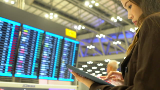 Woman use social media at airplane flight information board at airport