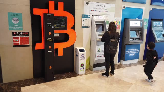 woman uses a bank atm next to a bitcoin atm machine at a shopping mall on april 16, 2021 in istanbul, turkey. turkey's central bank announced a ban... - cryptocurrency stock videos & royalty-free footage
