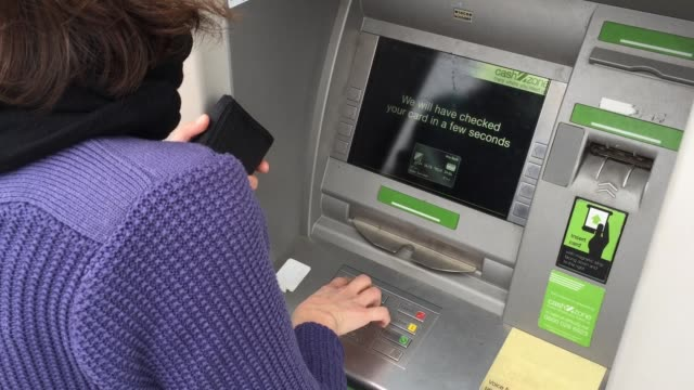 woman uses a cashpoint atm on november 3, 2017 in bristol, england. the bank of england raised interest rates from a historic low for the first time... - interest rate stock videos & royalty-free footage
