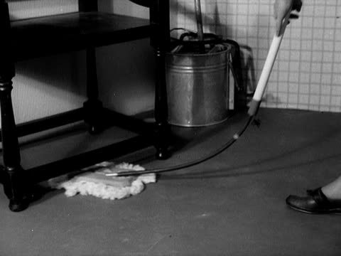 A woman uses a flexible floor mop in a kitchen
