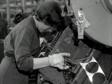 woman uses a machine to cut discs from a sheet of metal in a factory. 1960. - ディスク点の映像素材/bロール