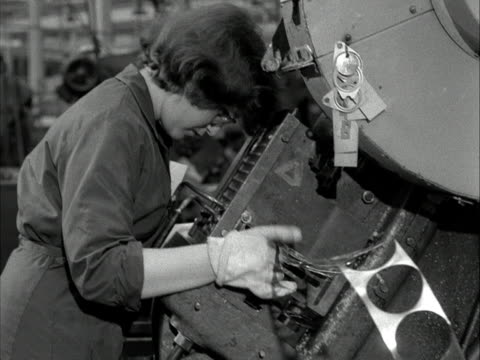 a woman uses a machine to cut discs from a sheet of metal in a factory 1960 - sheet metal点の映像素材/bロール