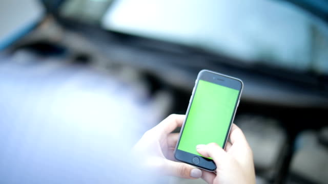 woman uses a phone with a green background - snapping stock videos & royalty-free footage