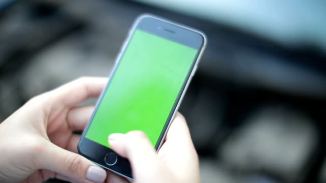 Woman uses a phone with a green background
