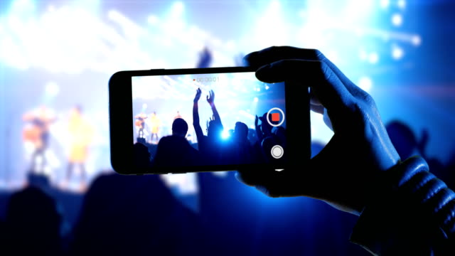 donna usa uno smartphone in un concerto musicale per registrare video dell'evento - generazione y video stock e b–roll
