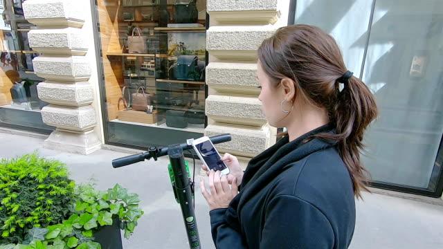 vídeos y material grabado en eventos de stock de mujer utiliza un teléfono inteligente para pagar el alquiler de un scooter eléctrico. - portability