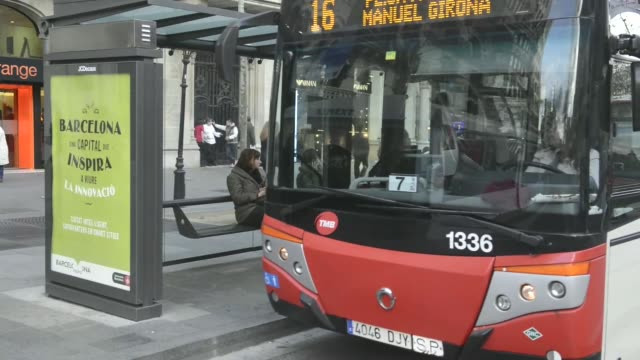 A woman uses a touch sreen information panel at a smart bus stop in Barcelona Spain on Thursday Feb 20 An elderly man checks his mobile phone at bus...