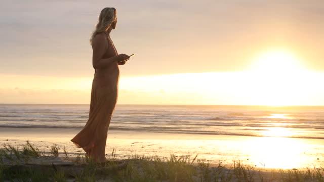 woman uses digital tablet above beach at sunrise, surf behind - オオハマガヤ属点の映像素材/bロール