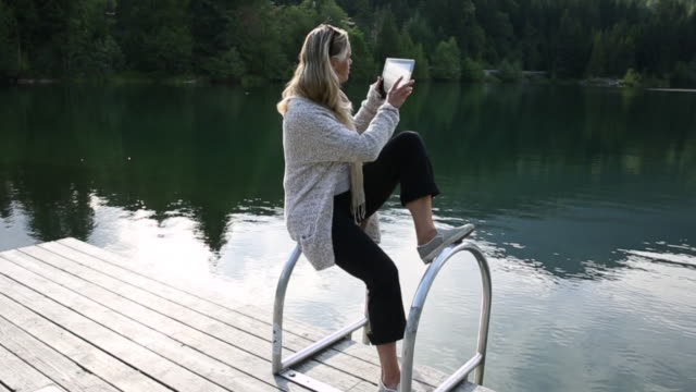 woman uses digital tablet, above mountain lake - technophile stock videos & royalty-free footage