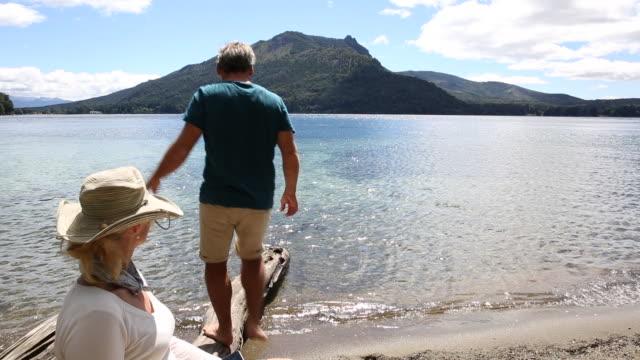 woman uses digital tablet at lake edge, man balances on log - computer equipment stock videos & royalty-free footage