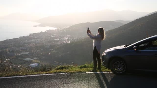 vídeos y material grabado en eventos de stock de woman uses digital tablet in front of car, above sea - photographing