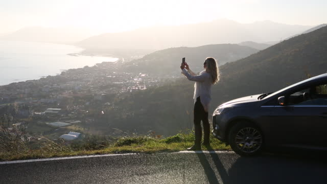 vídeos de stock e filmes b-roll de woman uses digital tablet in front of car, above sea - fotografando