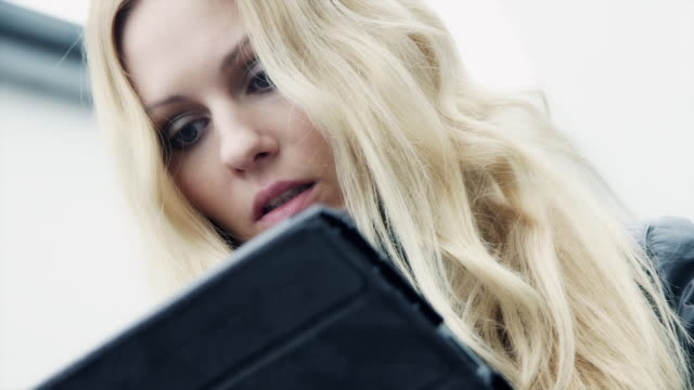 A woman uses her digital tablet and smiles.