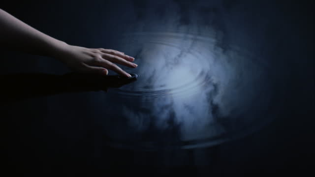 A woman uses her finger to create ripples in water reflected in a moonlit sky.