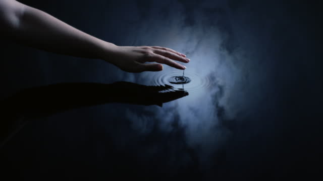a woman uses her finger to create ripples in water reflected in a moonlit sky.  - persona di sesso femminile video stock e b–roll