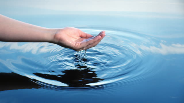 a woman uses her hand to collect water, letting it fall through her fingers which creates ripples reflected in a blue sky.  - concentric stock videos & royalty-free footage