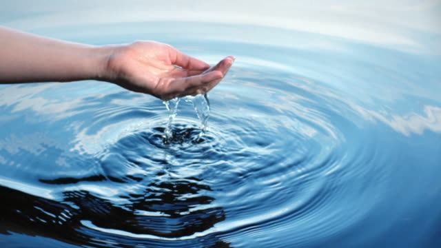 A woman uses her hand to collect water, letting it fall through her fingers which creates ripples reflected in a blue sky.